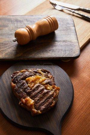 Photo pour Foyer sélectif de steak grillé savoureux servi sur des planches de bois avec couverts et moulin à sel - image libre de droit