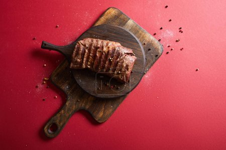 Photo for Top view of tasty grilled steak served on wooden boards on red background with pepper and salt - Royalty Free Image