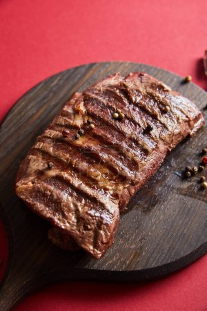 tasty grilled steak served on wooden boards on red background with pepper