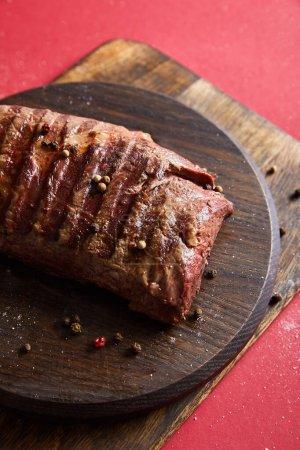 Photo pour Savoureux steak grillé servi sur des planches en bois sur fond rouge avec poivre et sel - image libre de droit