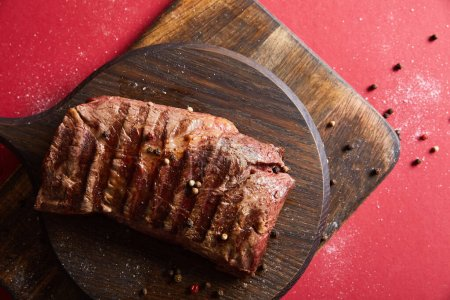 Photo for Top view of tasty grilled steak served on wooden board on red background with pepper and salt - Royalty Free Image