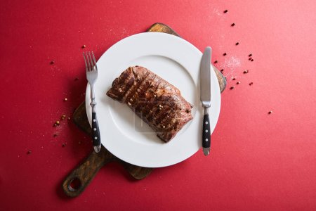 Photo for Top view of tasty grilled steak served on plate on wooden board on red background with pepper and salt - Royalty Free Image