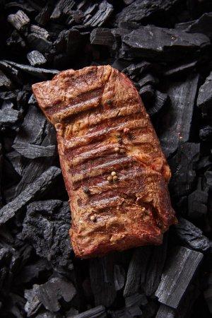 Photo pour Vue de dessus de steak grillé frais savoureux sur les charbons noirs - image libre de droit