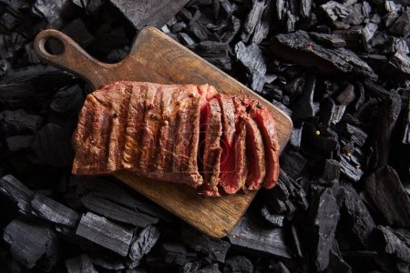 Photo for Top view of cut fresh grilled tasty steak with rare roasting on wooden cutting board on black coals - Royalty Free Image