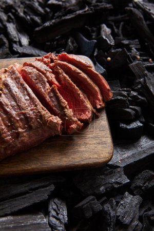 Photo for Cut fresh grilled tasty steak with rare roasting on wooden cutting board on black coals - Royalty Free Image