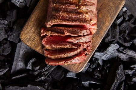 Photo pour Top view of cut fresh grilled tasty steak with rare rasting on wooden cutting board on black coals - image libre de droit