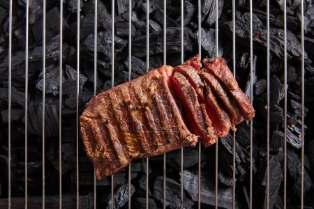 Photo for Top view of cut fresh grilled tasty steak with rare roasting on grate above black coals - Royalty Free Image
