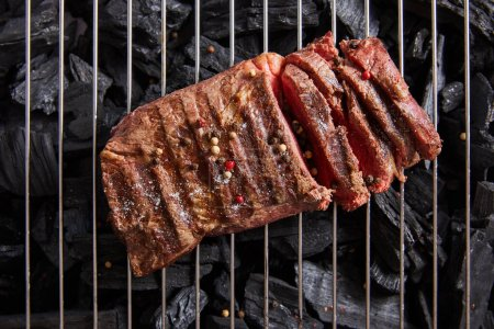 Photo for Top view of cut fresh grilled tasty steak with rare roasting and condiments on grate above black coals - Royalty Free Image
