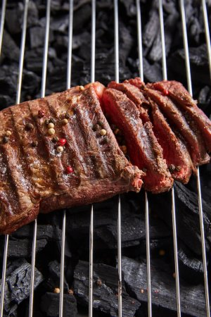 Photo for Cut fresh grilled tasty steak with rare roasting and condiments on grate above black coals - Royalty Free Image