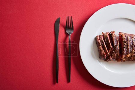 Photo for Top view of tasty grilled steak served on plate with cutlery on red background - Royalty Free Image