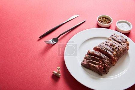 Photo pour Savoureux steak grillé servi dans une assiette avec couverts et sel et poivre dans des bols sur fond rouge - image libre de droit