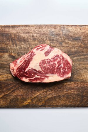 Photo for Top view of fresh raw steak on wooden cutting board on white background - Royalty Free Image