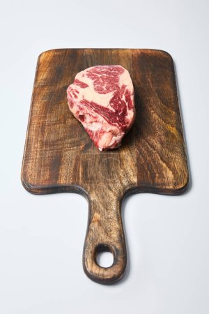 Photo for Fresh raw steak on wooden cutting board on white background - Royalty Free Image