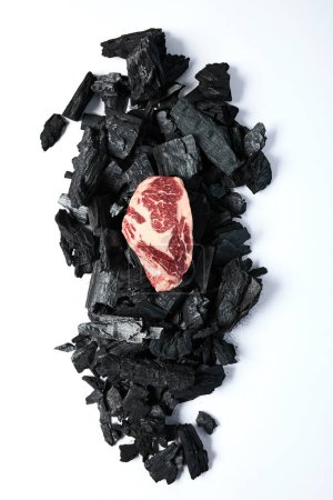 Photo for Top view of fresh raw steak on black coals on white background - Royalty Free Image