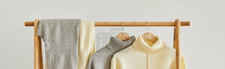 Photo for Beige knitted soft sweater and pants hanging on wooden hanger on white background - Royalty Free Image