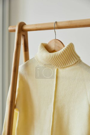 Photo for Close up view of beige knitted soft sweater hanging on wooden hanger isolated on white - Royalty Free Image