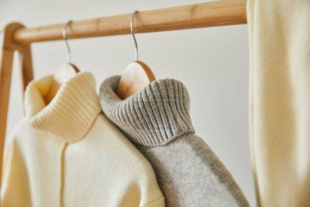 Photo pour Foyer sélectif de pulls doux tricotés beige et gris accrochés à des cintres en bois isolés sur blanc - image libre de droit