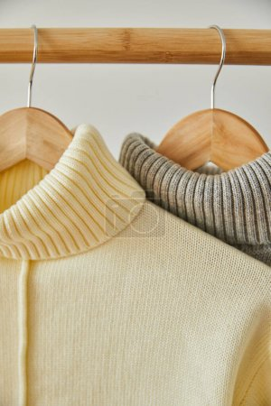 Photo for Close up view of beige and grey knitted soft sweaters hanging on wooden hangers isolated on white - Royalty Free Image