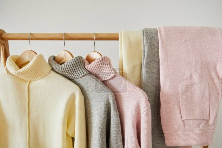 Photo for Close up view of pink, beige and grey knitted soft sweaters and pants hanging on wooden rack isolated on white - Royalty Free Image
