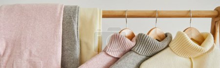 Photo for Close up view of pink, beige and grey knitted soft sweaters and pants hanging on wooden rack isolated on white, panoramic shot - Royalty Free Image