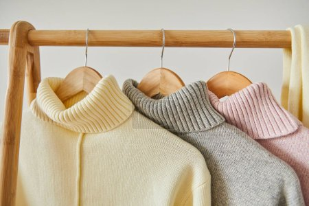 Photo for Close up view of pink, beige and grey knitted soft sweaters hanging on wooden rack isolated on white - Royalty Free Image