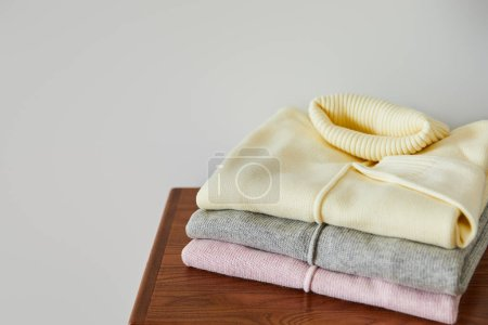 Photo pour Pull doux tricoté rose, beige et gris sur table en bois isolé sur blanc - image libre de droit