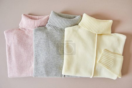 Photo for Top view of pink, beige and grey knitted soft sweaters - Royalty Free Image