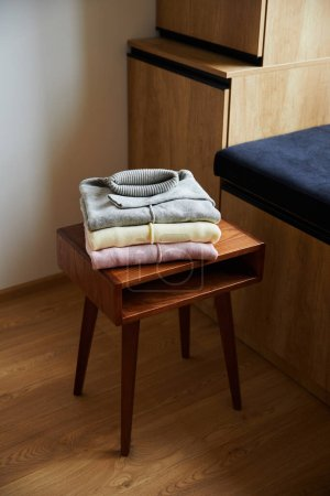Photo for Pink, beige and grey knitted soft sweaters on wooden table in room - Royalty Free Image