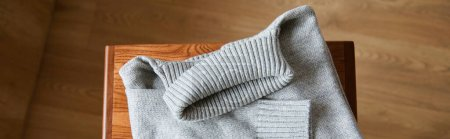 Photo for Top view of grey knitted soft sweater on wooden table in room, panoramic shot - Royalty Free Image