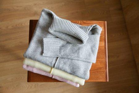 Photo pour Vue de dessus des pulls doux en maille rose, beige et gris sur la table en bois dans la chambre - image libre de droit