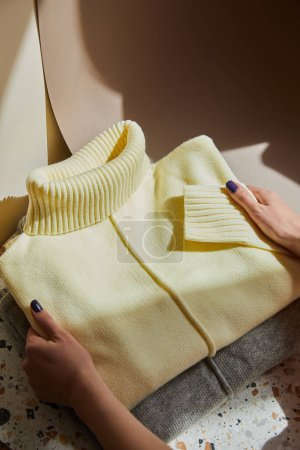 cropped view of woman holding yellow and grey knitted soft sweaters on stone and paper surface in sunlight