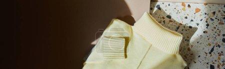 Ansicht von gelbem Strickpullover auf Stein- und Papieroberfläche im Sonnenlicht, Panoramaaufnahme