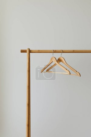 Photo for Close up view of empty hangers on wooden rack isolated on white - Royalty Free Image