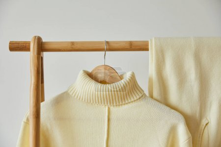 Photo for Close up view of beige knitted soft sweater and pants hanging on wooden hanger isolated on white - Royalty Free Image
