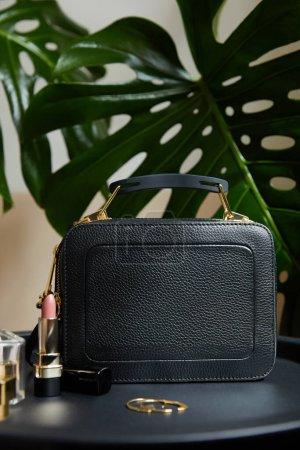 Photo pour Sac à main en cuir près des boucles d'oreilles dorées et rouge à lèvres sur table noire près des feuilles tropicales - image libre de droit