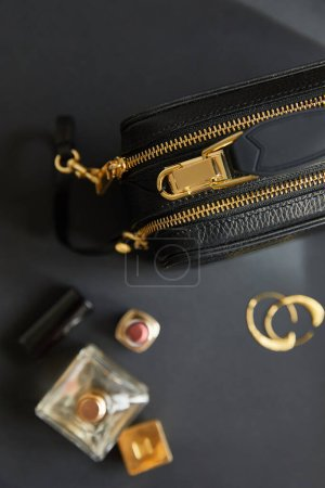 Photo pour Top view of leather handbag near golden earrings, parfum and lipstick on black table - image libre de droit