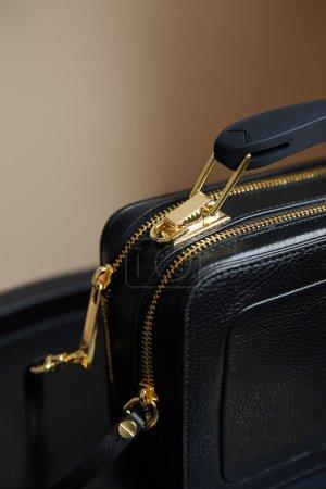 Foto de Vista cercana del bolso de cuero con cremalleras doradas sobre fondo beige - Imagen libre de derechos