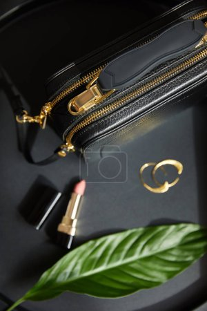 Photo pour Top view of leather handbag near golden earrings and lipstick on black table with green leaf - image libre de droit