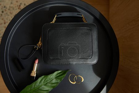 Photo for Top view of leather handbag near golden earrings and lipstick on black table with tropical leaf - Royalty Free Image