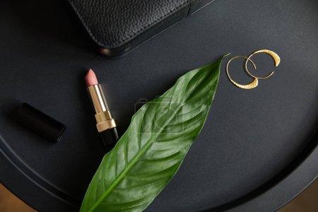 Photo pour Vue du dessus de boucles d'oreilles dorées et rouge à lèvres rose sur table noire avec feuille tropicale - image libre de droit