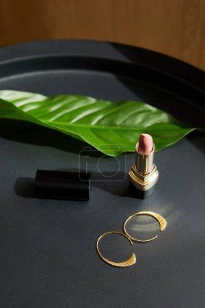Photo pour Boucles d'oreilles dorées et rouge à lèvres rose sur table noire avec feuille tropicale - image libre de droit