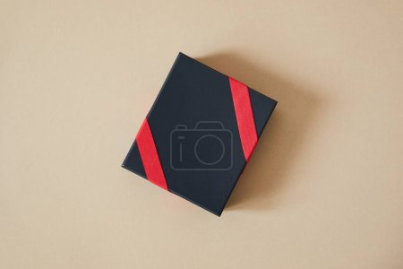 top view of black gift box with red ribbon on beige background