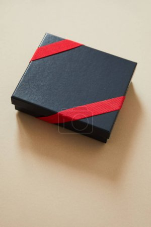 black gift box with red ribbon on beige background