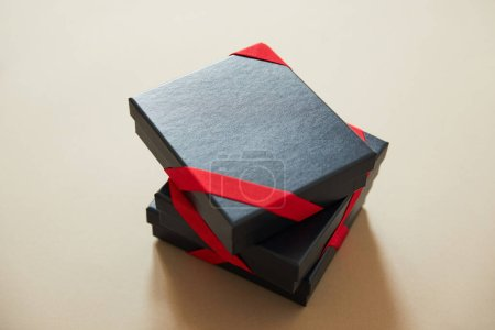 Photo for Black gift boxes with red ribbons on beige background - Royalty Free Image