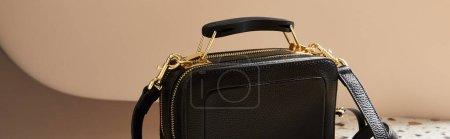 Photo pour Sac à main en cuir noir avec fermeture éclair dorée sur fond beige, panoramique - image libre de droit