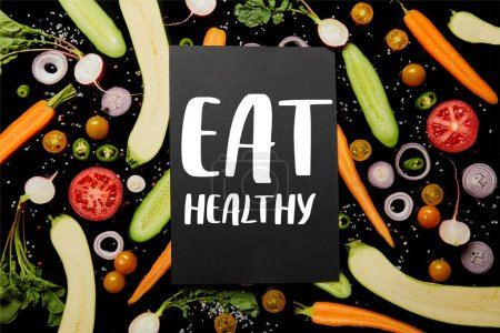 top view of black card with eat healthy illustration on vegetable pattern isolated on black