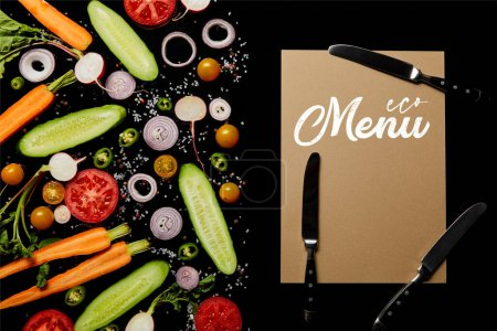 Photo for Top view of fresh vegetable slices with salt near paper card with menu illustration and knives isolated on black - Royalty Free Image