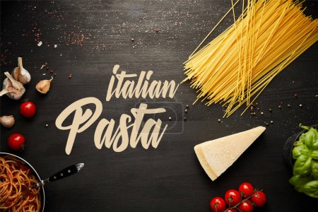 Photo for Top view of tasty bolognese pasta in frying pan near ingredients on black wooden background, italian pasta illustration - Royalty Free Image