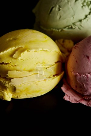 Photo for Close up view of delicious yellow, pink and green ice cream balls isolated on black - Royalty Free Image