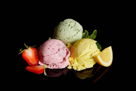 Photo for Delicious lemon, strawberry and mint ice cream balls isolated on black - Royalty Free Image